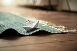 Kleines Papierschiff auf Teppich (Wellen)