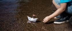 Kleiner Junge setzt kleines Papierschiff ins Wasser