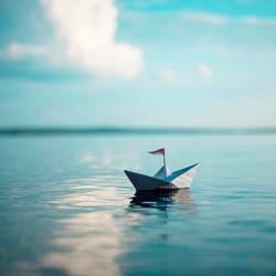 Papierschiff mit Flagge auf dem Meer