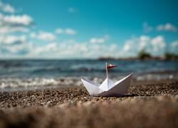 Boot aus Papier am Sandstrand