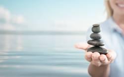 Keep Balance   Eine junge Frau balanciert einen Turm aus Steinen