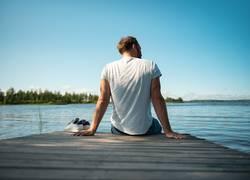 Mann sitzt auf Holzsteg am See in Finnland