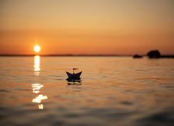 Sonnenuntergang am See mit kleinem Papierschiff