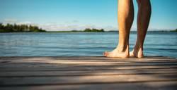 Mann steht Barfuß auf einem Holzsteg am See   Panorama