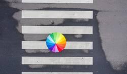 Fussgänger mit einem Regenbogen Regenschirm