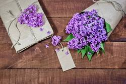 Gift and bouquet of lilacs on a wooden table
