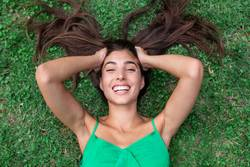 young cheerful woman lying down on the grass