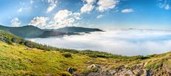 Panorama of green mountains in the clouds