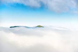 Green mountain peak in clouds
