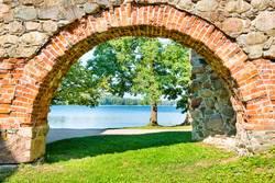 Brick arch and tree near lake