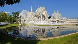 Beautiful ornate white Thai temple reflecting in water
