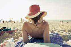 Mädchen mit Hut von hinten am Strand