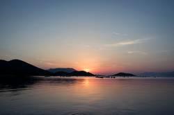 Sonnenuntergang am Meer mit Hügeln