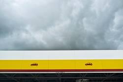 Vordach in gelb, rot und weiß mit Wolkenhimmel