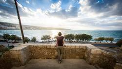 Young woman enjoys the view on the island of creta, greece.