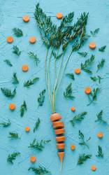 Carrot cut into slices on blue background. Flat lay.