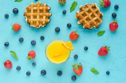 Waffles and red berries, orange juice and mint leaves