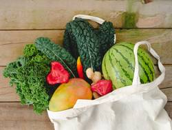 Cloth bag with vegetables on wooden background.