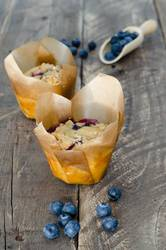 Muffins with blueberries on wooden background