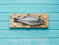 Sea bass on kitchen table with lemon and rosemary