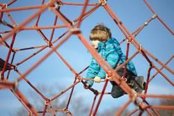 Junge klettert auf dem Spielplatz