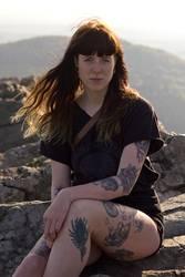 Carina | Junge tätowierte Frau sitzt auf Bergspitze