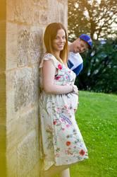 Schwangere Frau und lustiger Mann an einer Mauer