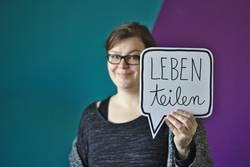 """Frau hält Sprechblase """"leben teilen"""""""