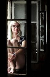Junge Frau sitzt an einem kaputten Fenster