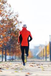 Rear view of a senior man in sport clothes jogging in the park