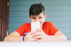 boy wearing red t-shirt sitting outdoors using phone