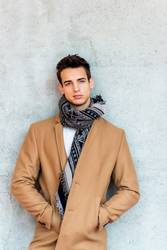 Trendy young man wearing coat and scarf leaning on a wall