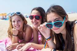 smiling girls best friends lying on beach while looking camera