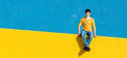 Young boy wearing casual clothes sitting on a yellow fence