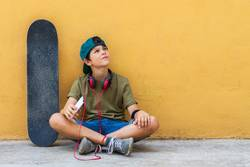 boy sitting on ground leaning on a wall while using a mobile