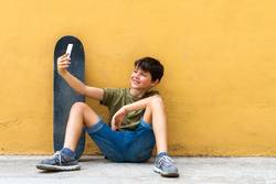boy sitting on ground leaning on a wall, taking a selfie