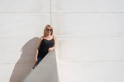 Blonde woman leaning on a white wall while looking camera