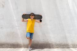Young smiling boy leaning on yellow wall holding a skateboard