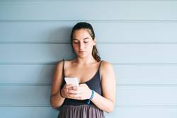 Beautiful young woman leaning on wall using a smartphone
