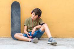 boy sitting against a yellow wall, listening music by headphones