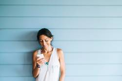 Beautiful woman leaning on wall while using smartphone