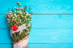 White flower bouquet with a red heart on a blue background.