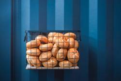 Bread buns in a basket hanging on a blue wall