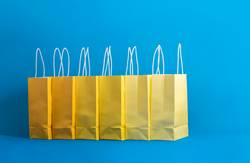 Yellow shopping bags on a blue background, Shopping concept