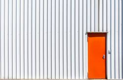 Orange metal door and a white warehouse wall