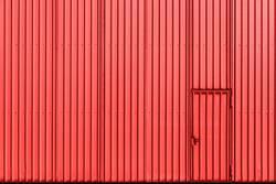 Industrial building facade with red metal wall and door