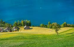 Green fields and blue lake in Swiss village