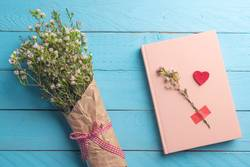 White flowers bouquet and pink notebook