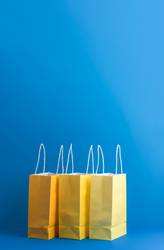 Three shopping paper bags on blue background. Xmas shopping