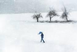 Snowstorm scenery. Man walking through snowfall. Winter weather